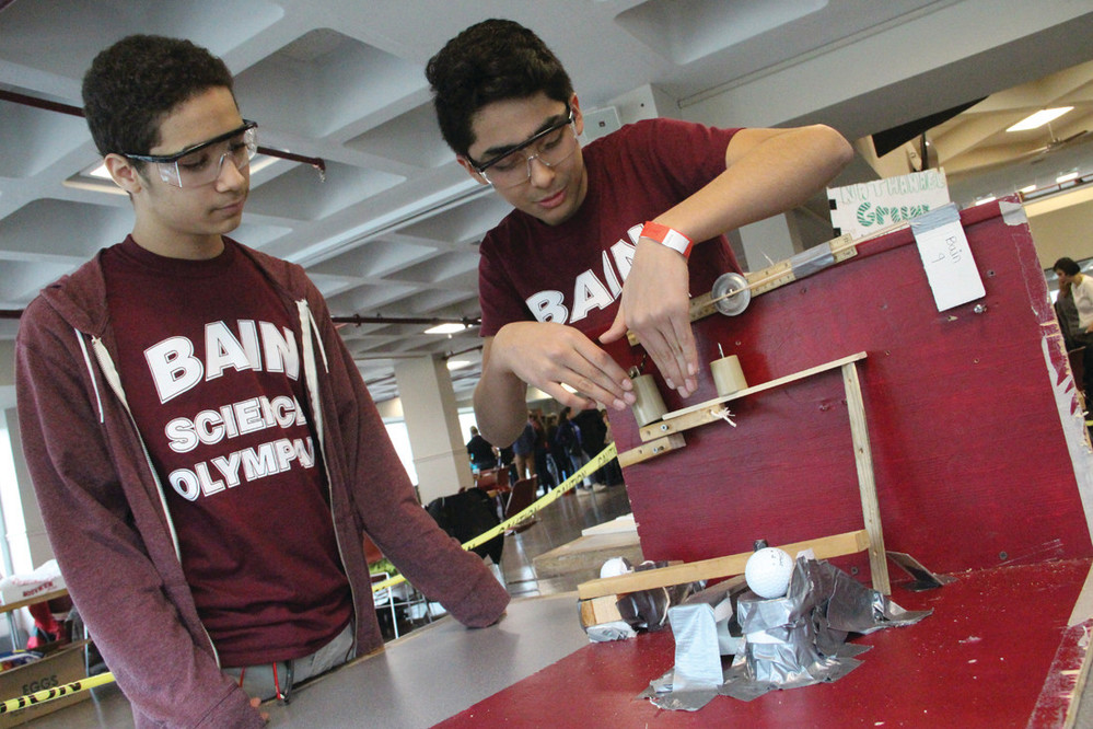 BUT WILL IT WORK? Bain School eighth-graders Ivan Abreu and David Quevedo explain the contraption they designed that sends a golf ball through a series of passages before knocking out a post that lowers weights to lift a flag.