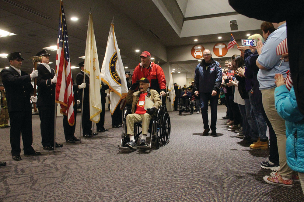 THEIR SERVICE RECOGNIZED: Accompanied by Russell DesGrange, who served as his guardian, WWII veteran Irwin Kaplin of Wakefield is saluted as he arrives at Green Airport for Saturday's honor flight to Washington, D.C.