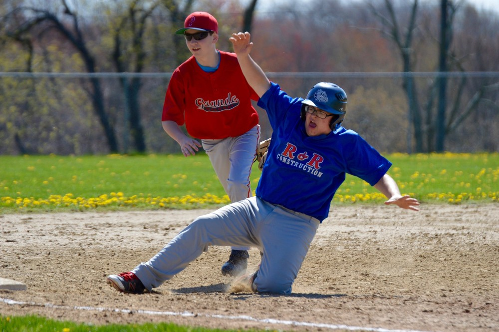 Jesse Almeida of R&R Construction slides into third as he's hotly pursued by the Grande Masonry third baseman, Zach Sherman, during a Portsmouth Babe Ruth game Sunday morning at Glen Farm.