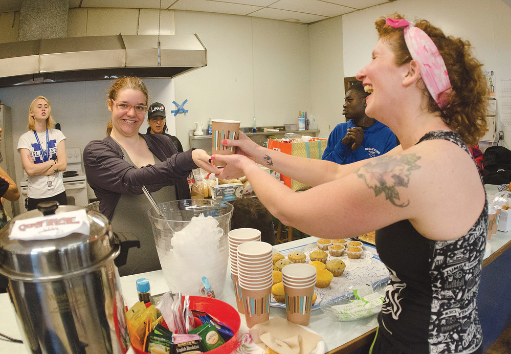 Tess Deleo (left) of Portsmouth serves a drink to Zumba instructor Amy Hart at the CFP Cafe in the Common Fence Point Community Hall last week. Ms. Hart is also a speech pathologist who was instrumental in starting up the cafe, at which people with special needs volunteer.