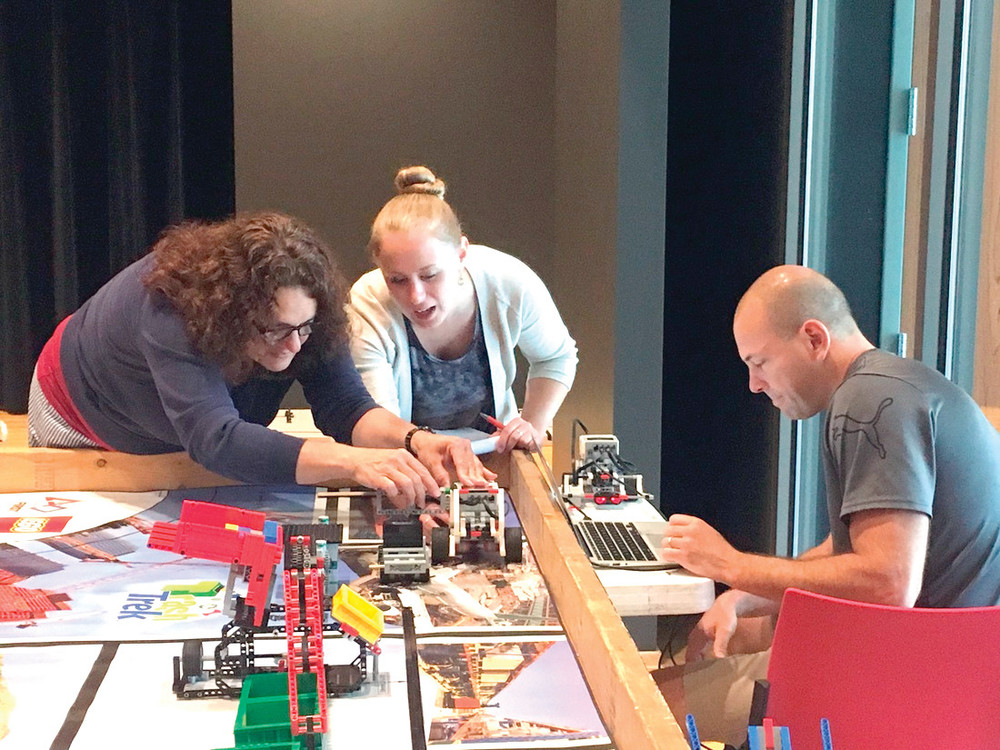 LEARNING BRICK BY BRICK: Teachers Sophia Michalopoulos, Rachael Franklin and Dan Villard collaborate on a robotics challenge during the 2016 LEGO Robotics course offered by Rhode Island Students of the Future. The organization is offering a professional development course July 31 to August 2 for teachers, librarians, after school providers and parents. For more information, visit www.risf.net.