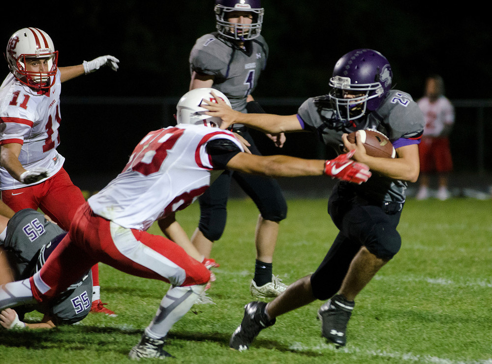 Huskies quarterback Matt DeFelice (middle) looks on as running back Dylan Martins holds off a Townies tackler for a short gain in their game at Mt. Hope High School on Friday night. Martins scored a touchdown during the game.