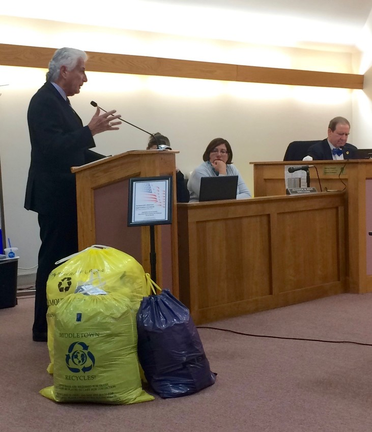 Bob Moylan, former public works commission in Worcester, tells the Town Council how a pay-as-you-throw system benefitted his city after it was adopted 22 years ago. On the floor are three examples of bags Portsmouth residents participating in the system will use.