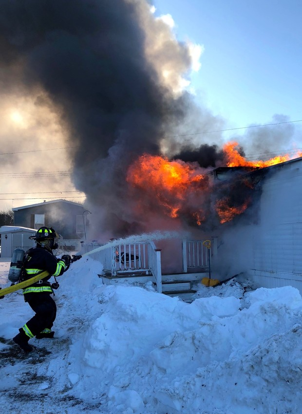 A firefighter battles a blaze that destroyed a North Drive mobile home at Sunny Acres in Portsmouth Sunday morning.