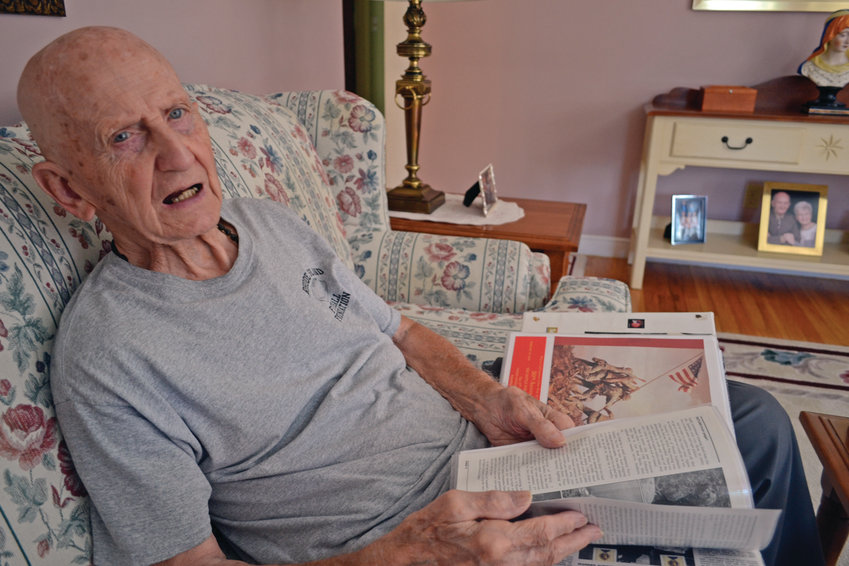 GOING STRONG: D-Day and Iwo Jima veteran Ray Raiche has accumulated enough historical information and photographs to fill 22 albums. He leafs through one here while sitting on his couch in his Warwick home. At 93 years old, he will be the youngest Iwo Jima survivor to participate in the Bristol 4th of July Parade.