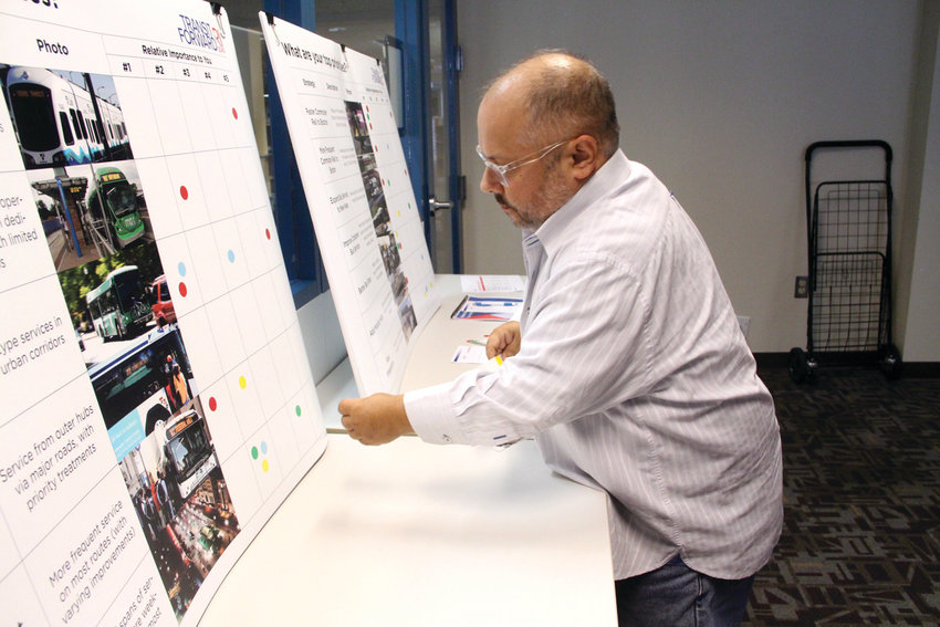 """RANKING THE OPTIONS: At left, Frank Susa of Warwick, who uses RPITA buses frequently, places a sticker to indicate a service he favors following the """"Transit Forward RI 2040"""" workshop."""