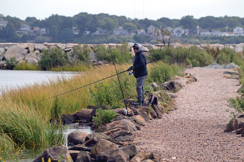 NEW LIFE: A fisherman (who declined to identify himself) peacefully watches his lines from the newly refurbished causeway leading to the breakwater at Salter Grove Memorial Park while finishing up a morning of fishing.