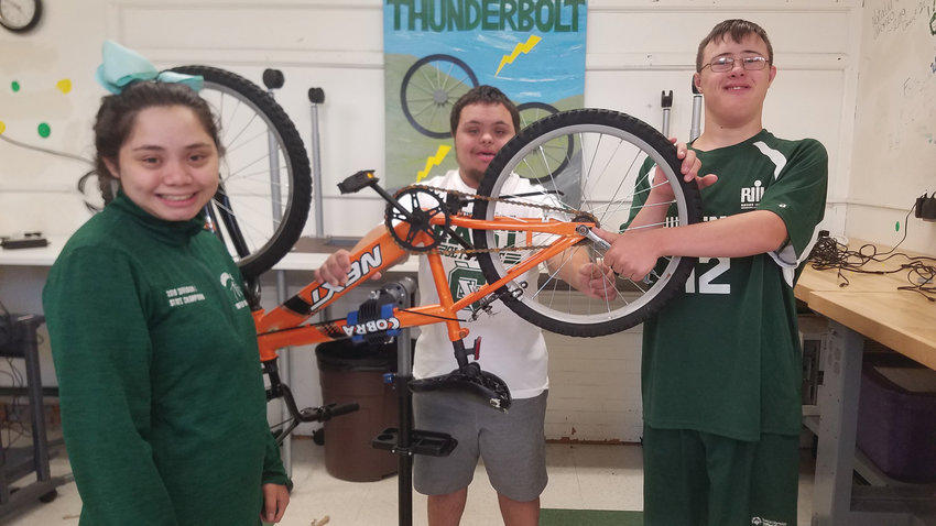 BIKE SHOP: Emily Sanita, James Hayden and Dylan Needham share a moment in Cranston East's Thunderbolt Bike Shop.