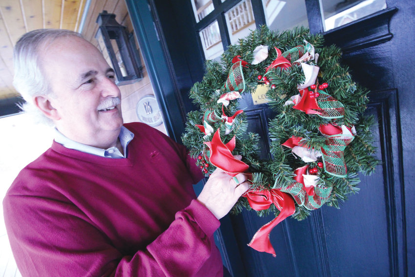 "GETTING IN THE SPIRIT: J. Michael Levesque, a former West Warwick mayor who now resides in Warwick, hangs a wreath on the door of his home. ""Lost in the hustle and bustle (and the pressure) of Hollywood and Wall Street-inspired gift giving,"" he says, ""are the times of reflection on the true meaning of the holiday."""