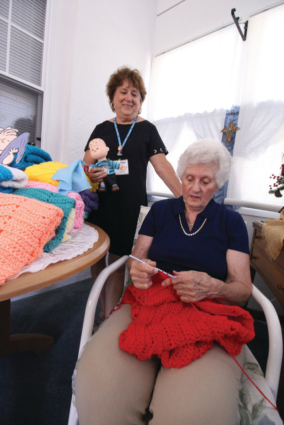 'THERE'S A STORY HERE': Those were the words of Martha Sholes (standing), Rhode Island coordinator of Project Linus, who wanted to shine a spotlight on her friend, Helen Smith, who celebrates her 85th birthday this week and has been such a contributor to the project.