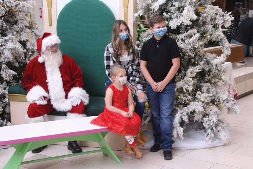 THEY ALL SMILED: It was difficult to tell, but behind their masks, Jayden, Christopher and Lillian Buonanno were all smiling for their photo with Santa.