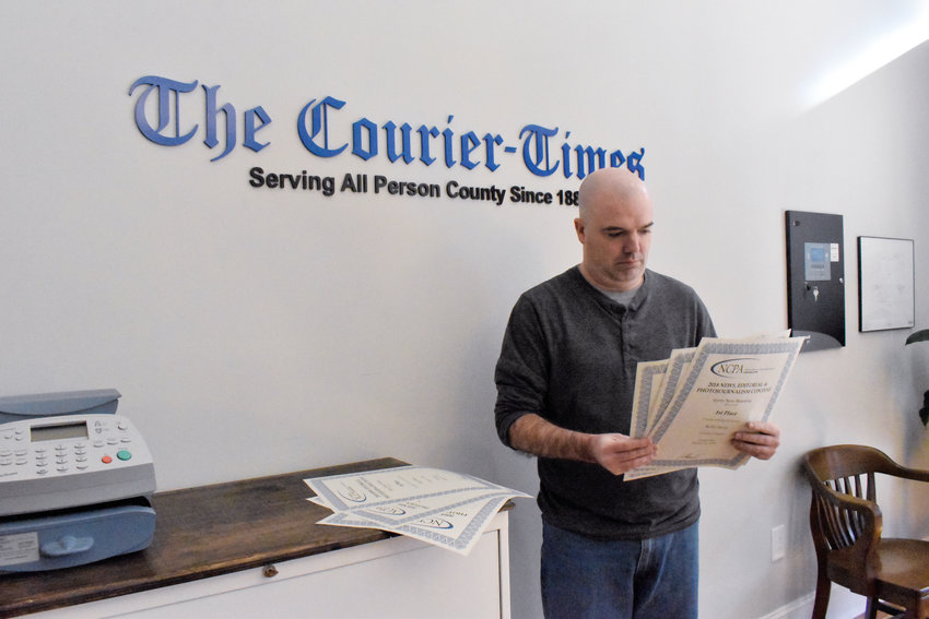 C-T sports editor Kelly Snow looks over some of the six editorial awards he received Thursday night at a ceremony in Raleigh. Four of his awards were first place awards.