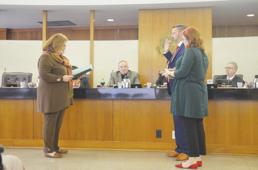 Person County Clerk of Court Deborah Barker reads Benji Gault's oath of office while Gault's wife, Chelsea, holds the Bible at the City Council meeting Monday.