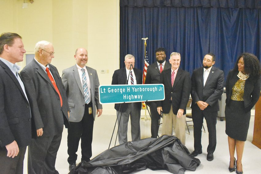 Inclement weather pushed the dedication ceremony for the new Lt. George H. Yarborough Jr. Highway indoors, but smiles were on plentiful display Monday afternoon as the new highway sign was unveiled.Pictured, from left, are Rep. Larry Yarborough, Harold Davis, DOT district 5 engineer Joey Hopkins, County commissioner David Newell, Keifer Wynn, standing in for U.S. Rep. Mark Walker who was not in attendance, county commissioner Gordon Powell, Commissioner Ray Jeffers and Board of Transportation member Valerie Jordan.