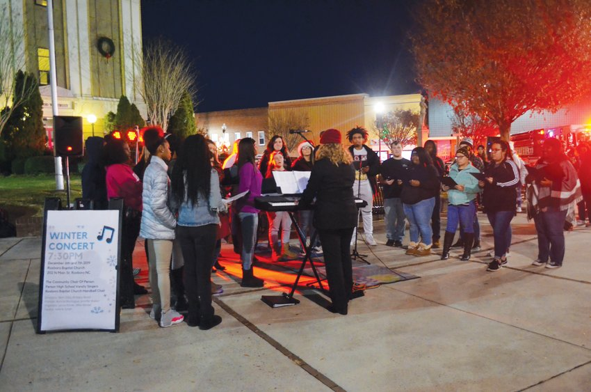 The Person High School Choral Ensemble, led by director Brittany Booth, performs in front of the Person County Courthouse Thursday night for Jingle on Main.