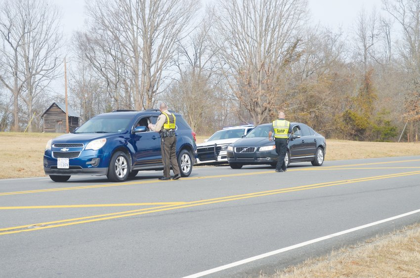 A Sheriff's deputy and a State Highway Patrol Trooper hand out fliers with information on Danny Holt at the intersection of Highway 501 and Shiloh Church Road near where Holt went missing Friday, Dec. 20.