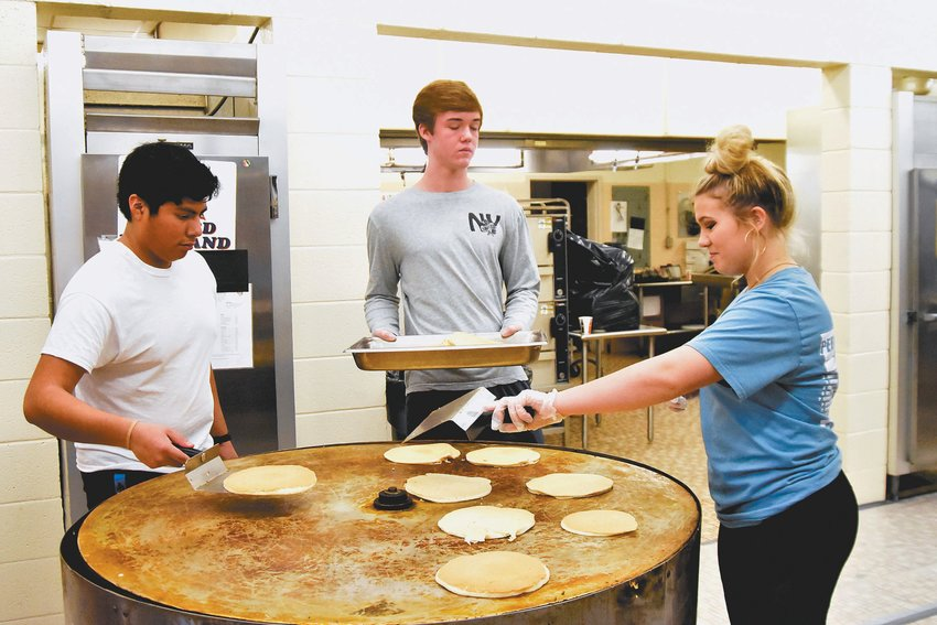 From left, Frank Garcia-Perez, Ridge Clayton and Grayson Brann collect pancakes off the griddle during Saturday's Kiwanis Club Pancake Jamboree.