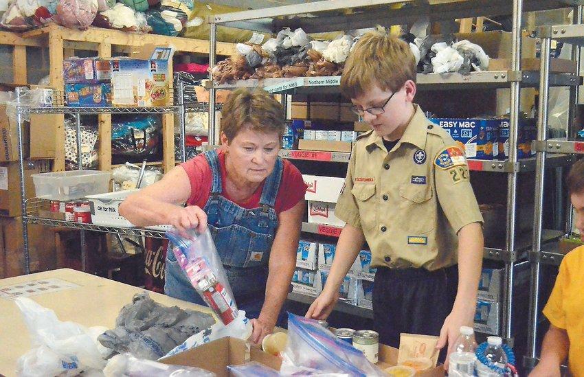 The coordinator for Backpack Pals, Susan Hester, helps Nathan Davis pack food last Wednesday.