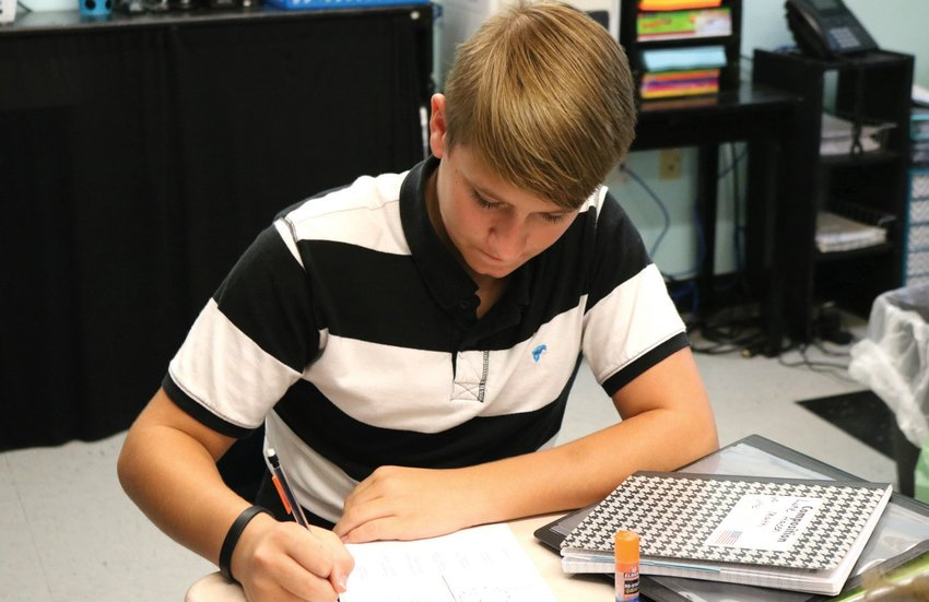 Eighth grade student Luke Haden works in math class in a striped polo. GRACE PRYOR | BULLHORN