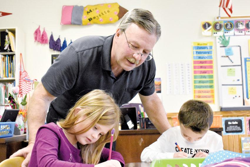 Principal Stephen Hester makes his rounds through first-grade classrooms, helping Leah Sumner and Carter Toone with their work.
