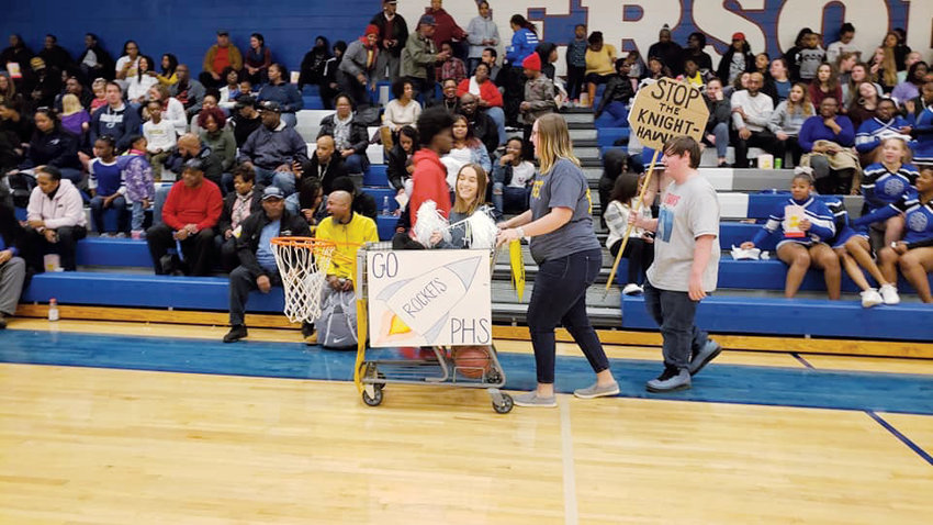 Contributed Photo .Delaine Phelps is seen here pushing a shopping cart with Grayson Cothran inside.  These two Person High School tennis players are parading a cart that promotes Rocket Pride..