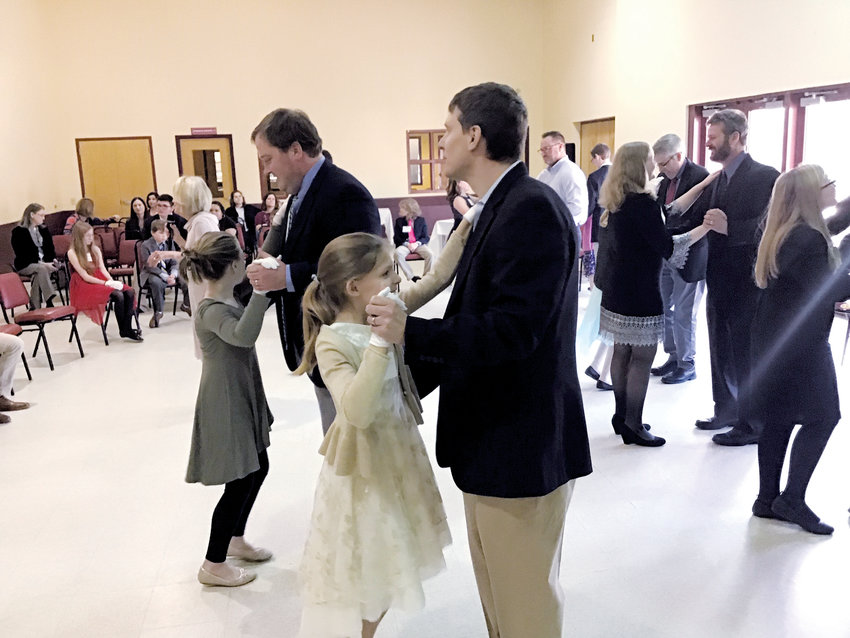 Cece Fitzgerald, left, and her father Hunt Fitzgerald, and Lilly Atkins and her father Chris Atkins, practice their Father/uaughter waltz during the National Junior Cotillion's Dip into Dance class.