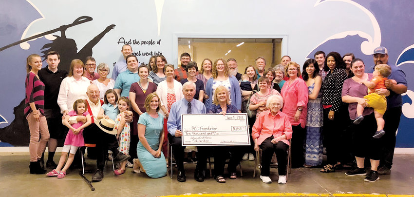 Billy Horner, seated front row center, and his wife, Patricia Knott Horner, celebrated the creation of the Patricia Knott Horner Scholarship with family and friends during a recent event at the My Life Matters warehouse.