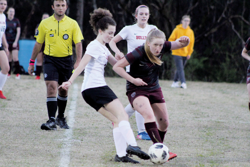 Contributed Photo.Roxboro Community School's Emily Taylor tries to take the ball away from an East Wake Academy player during this week's game.