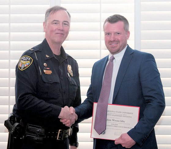 Adam Irby, right, accepts the congratulations of Apex Chief of Police John Letteney, after completing the Law Enforcement Executive Program.