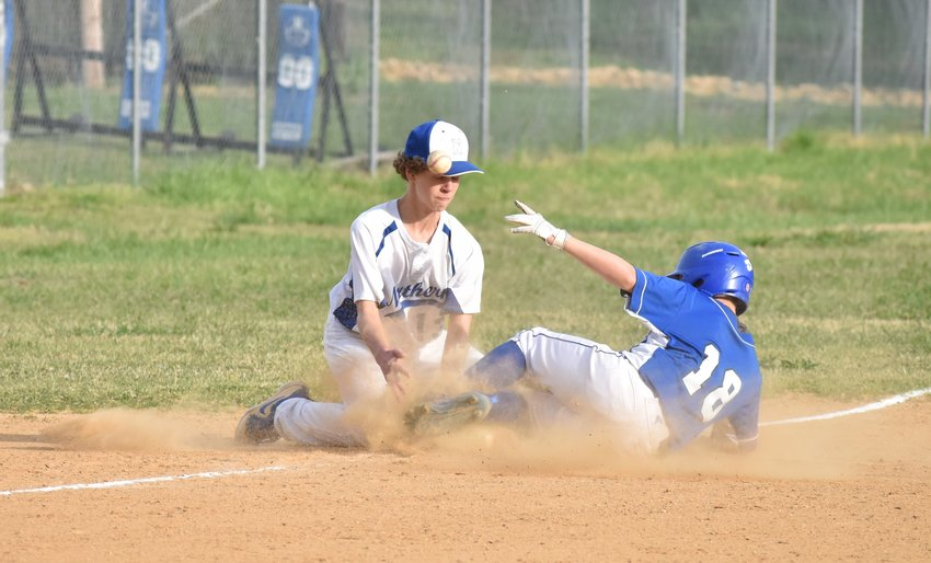 Southern's Levi Strader slides into third just before Northern third baseman Lee Womack can make the catch and apply the tag.