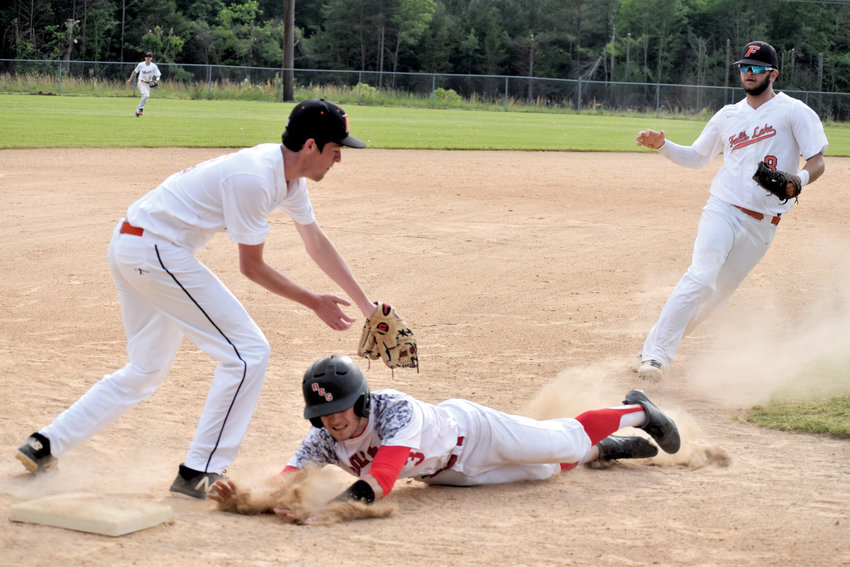 Kelly Snow | The Courier-Times.Roxboro Community School's Michael Clayton slides under the tag during a rundown in Saturday's game against Falls Lake Academy..