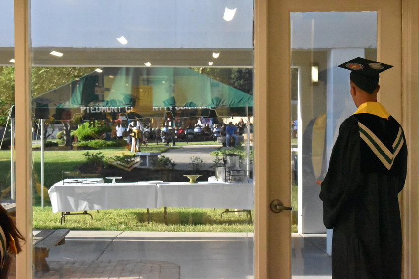 Nathan Matherly looks out over the growing crowd in a quiet moment before PCC's graduation ceremony.