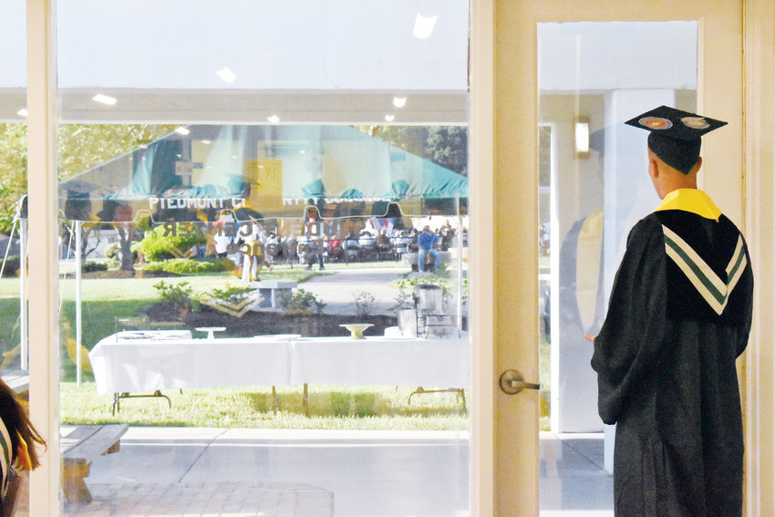Nathan Matherly watches as the crowd grows in the courtyard at Piedmont Community College before Friday night's commencement ceremony.