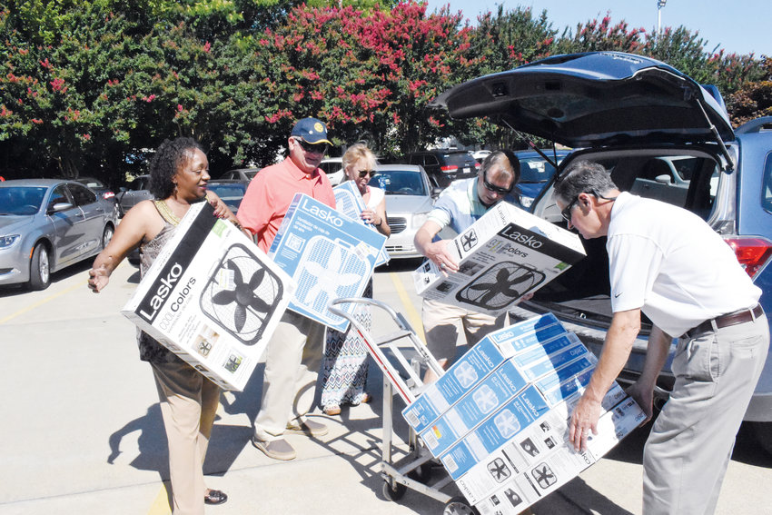 Person County Senior Center staffer Loretta Massey, left, helps Roxboro Rotary Club members, Stan Morton Dyan Suitt, Robert Allen and Bayard Crumpton unload fans donated by the club for a giveaway program run by the senior center. High temperatures this weekend will make staying cool a priority for many.