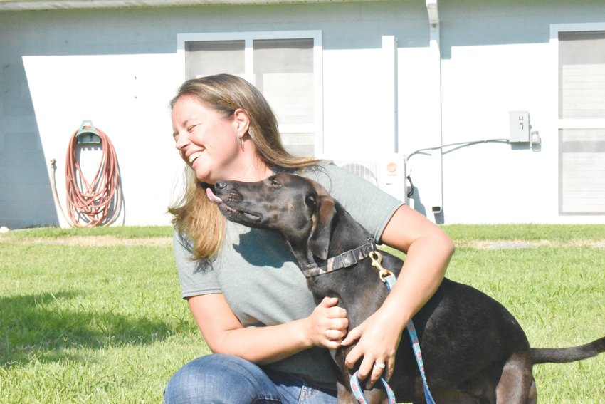 Kelli Oakley and one of her shelter dogs, Rambo, enjoyed a playful moment outside the Person County Animal Shelter Monday.