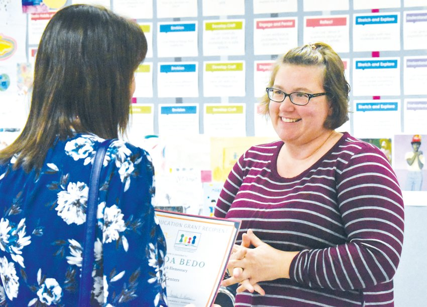 Stories Creek art teacher Amanda Bedo is all smiles as she learns from Amanda Morrow that she is the recipient of a special education grant from the Person County Education Foundation.