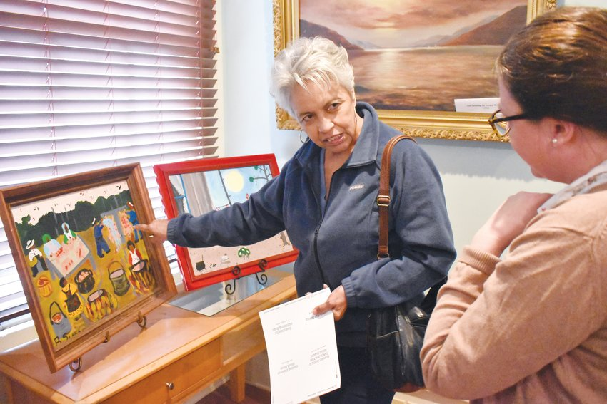 Person County Museum of History docent Angie Brown explains to museum director Carrie Currie a detail in one of the pieces of artwork on display this month at the museum as part of an observance of Black History Month.