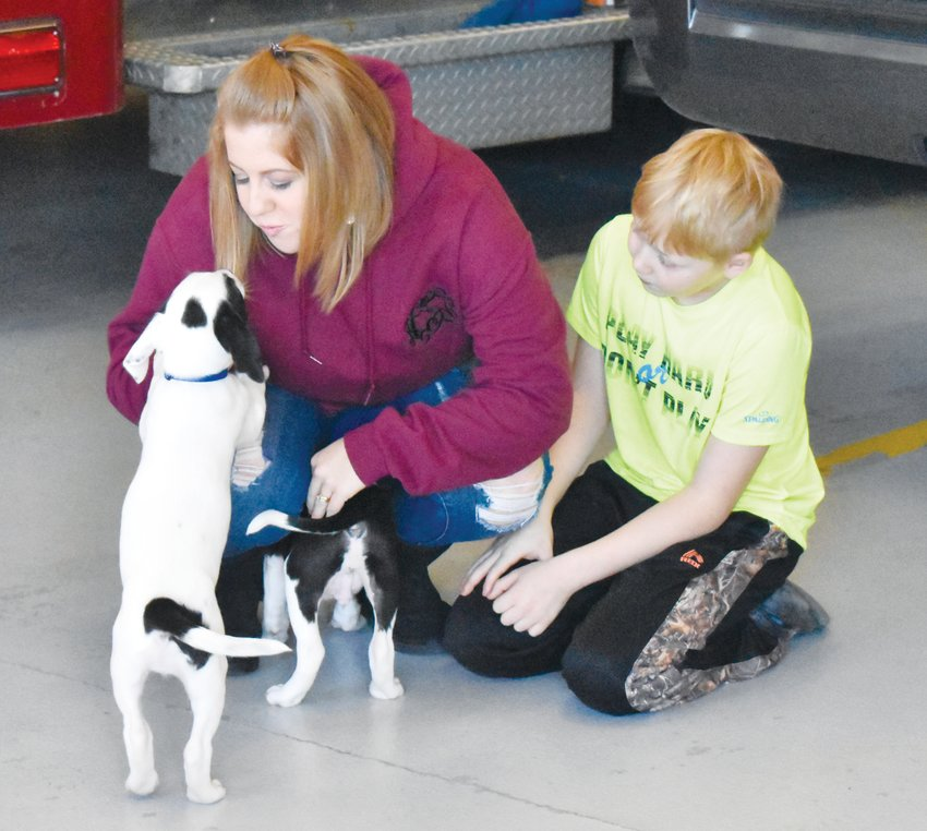 Amanda Solomon and her son Parker, 9, play with two of the puppies adopted Saturday by the families of Roxboro firefighters.