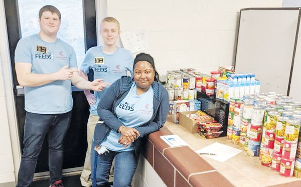 "PCC students make food drive fun with ""Souper Bowl"" theme; Zachary Walker, Jonathan Willis, and Latisha Springfield are shown with food collected during the campaign."