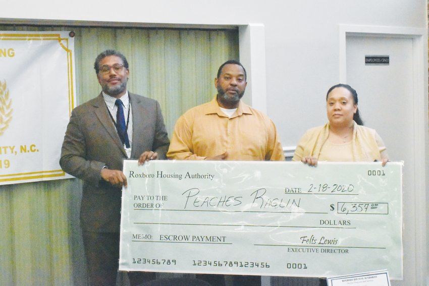 Peaches Raglin, right, is presented with an escrow payment from RHA Executive Director Felts Lewis, left, and FSS Coordinator Larry Mayfield. Raglin graduated from the FSS program on Feb. 18.
