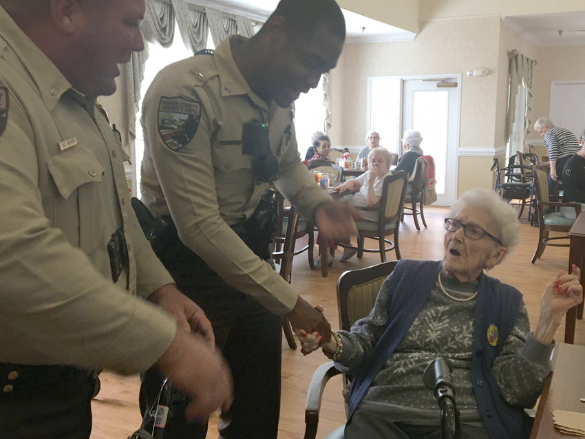 """Deputies RD Weaver and Tevin Dixon prepare to """"arrest"""" Ruth Bryant to cross the item of the 100-year-old's bucket list."""