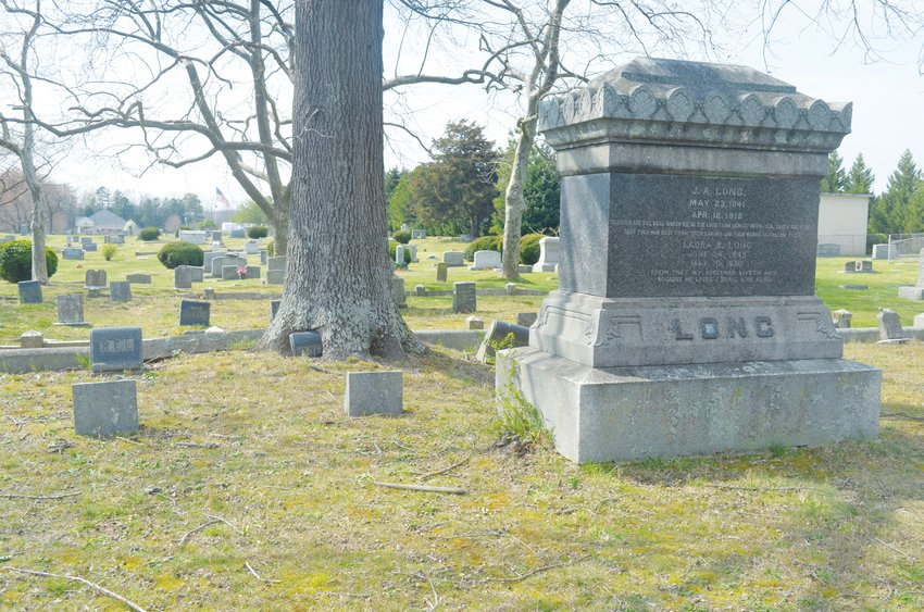 A tree has grown aroung a gravestone in the J.A. Long plot at Burchwood Cemetery. The tree could be cut down, but it would take an act of Roxboro City Council.