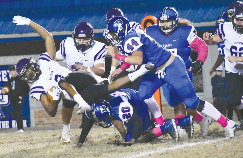 The Rockets' Preston Carr (44) and AJ Terrell (20) combine on a tackle in the Oct. 18 contest between Person and Northern Guilford.