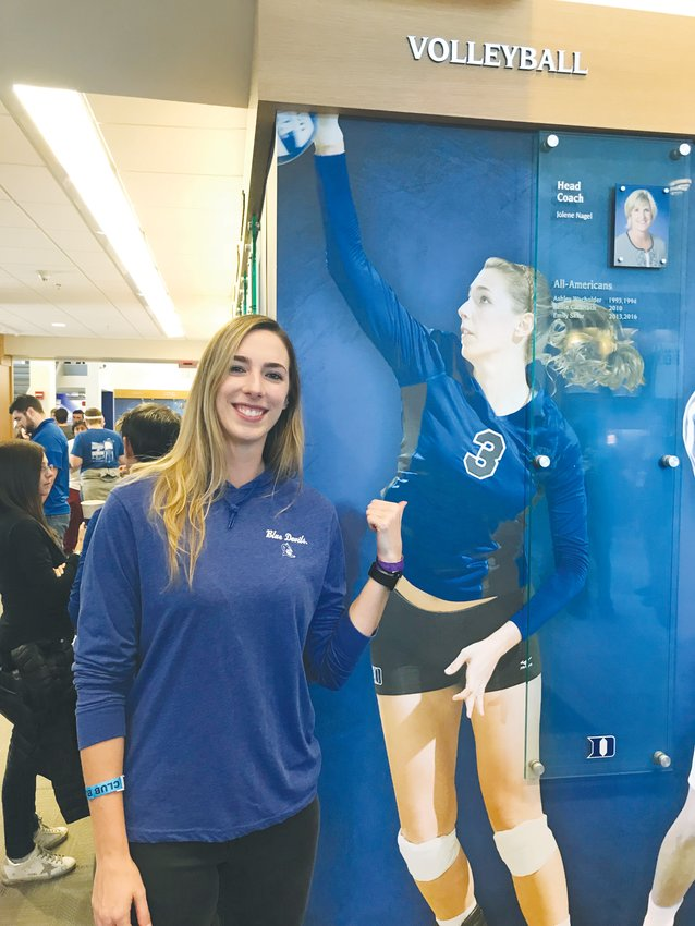 Amanda Robertson takes a picture next to herself on a wall at the Duke Hall of Fame.