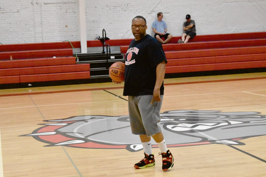 Earl Bailey watches his players participate in dribbling exercises at the beginning of workouts on Tuesday, July 7. Bailey, the head women's varsity basketball coach at the high school, plans to expand workout regimens in succeeding weeks, which increasingly develops an expreince factor for a team full of freshmen and sophomores.
