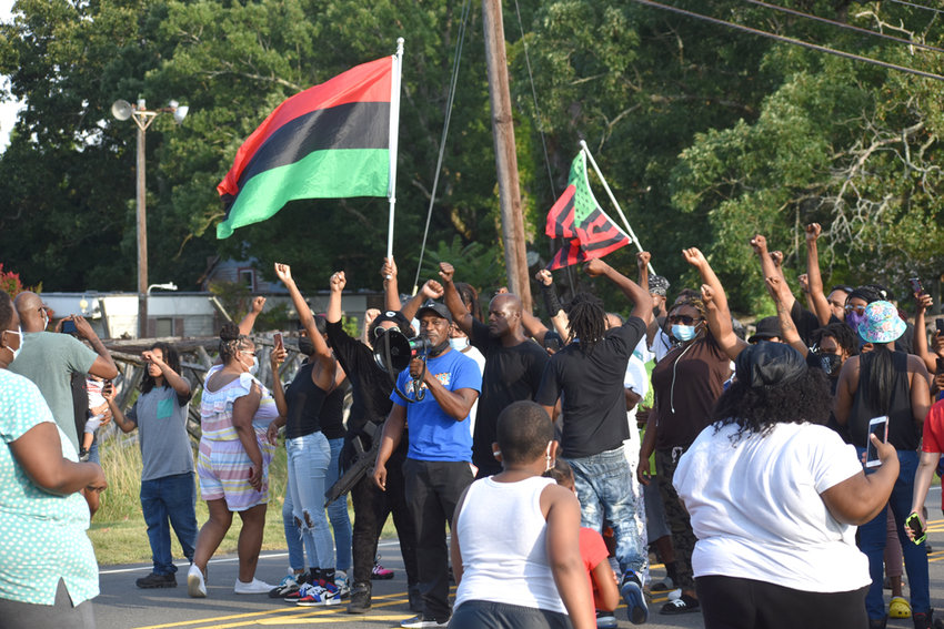 Jerriminco Brooks, center blue shirt, leads protesters in blocking Off Old Durham Road Wednesday.