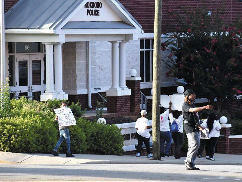Protesters march past the Roxboro Police Department Sunday.