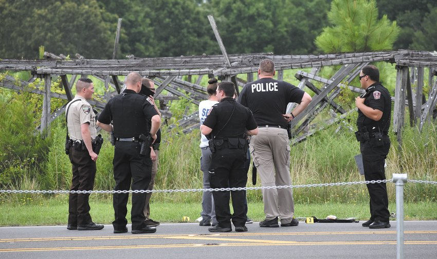 Officers from the Roxboro Police Department, Person County Sheriff's Department and the State Bureau of Investigation investigate the scene on Old Durham Road after the shooting of David Brooks Jr. Friday, July 24.