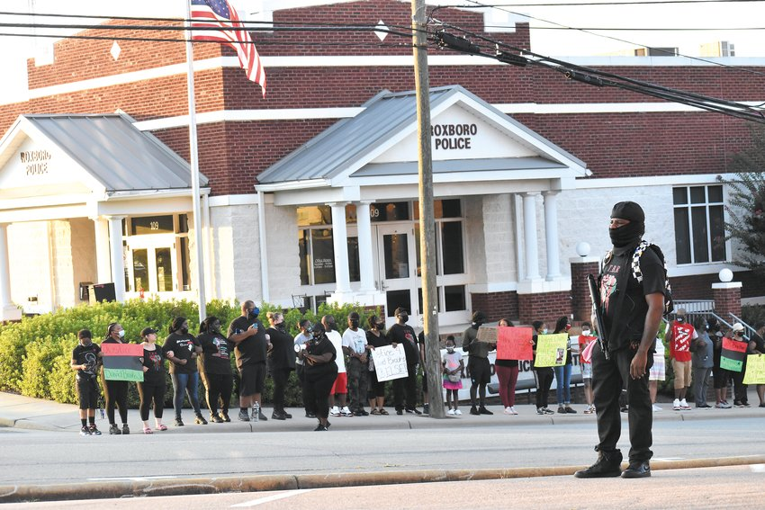 Demonstrators locked arms and held signs on the sidewalk in front of the Roxboro Police Department during Friday's protest in Uptown Roxboro.