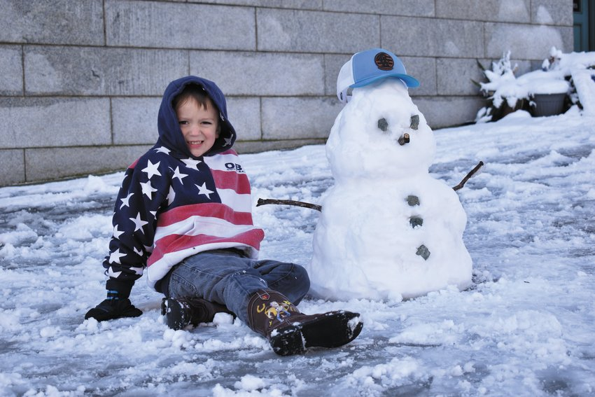 Preston Wesley poses with a snowman he made in Uptown Roxboro Thursday.